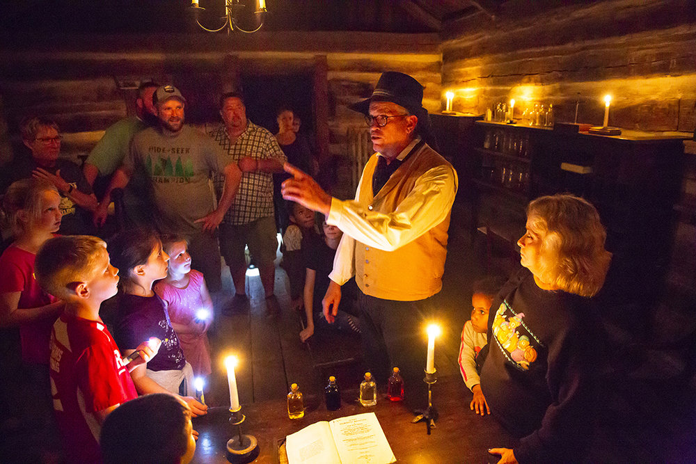 Dr. Craig Nelson, a retired physician from Chicago, explains to visitors how crude medical care for pioneers would have been in Abraham Lincoln's time during the annual candlelight walk through Lincoln's New Salem State Historic Site Friday, Oct. 5, 2018 in Petersburg, Ill. Nelson, a volunteer, was in the medical office of Dr. Francis Regnier, one of the village's two doctors. The candlelight walk continues tonight and Sunday from 7-9 p.m. [Rich Saal/The State Journal-Register]