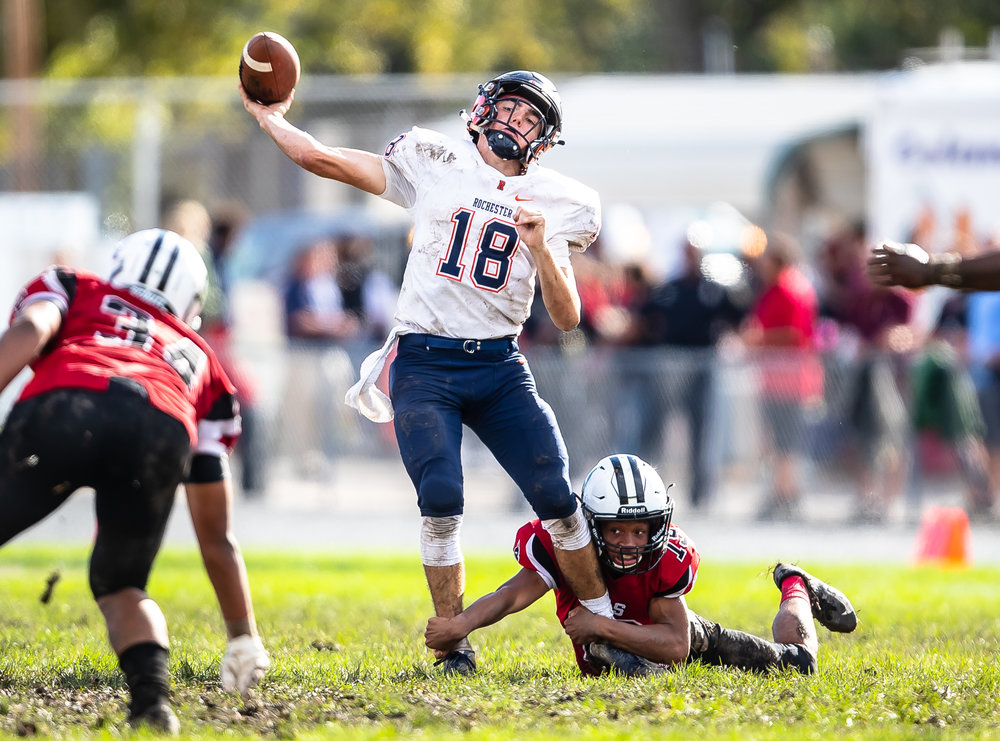 Rochester quarterback Clay Bruno (18) gets off a pass as he is tries to escape the sack from Springfield's Jesse Stewart (19) in the second half at Memorial Stadium, Saturday, Oct. 6, 2018, in Springfield, Ill. [Justin L. Fowler/The State Journal-Register]