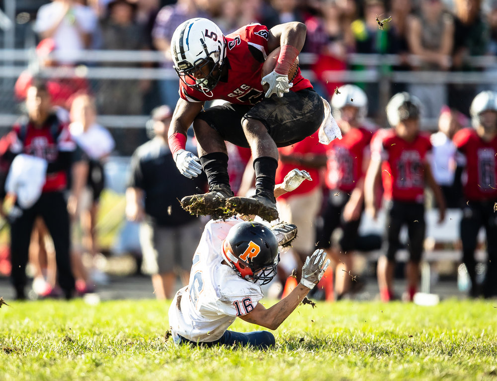 Springfield's Justin Bivins II (5) hurdles Rochester's Logan Peters (16) on a rush in the second half at Memorial Stadium, Saturday, Oct. 6, 2018, in Springfield, Ill. [Justin L. Fowler/The State Journal-Register]