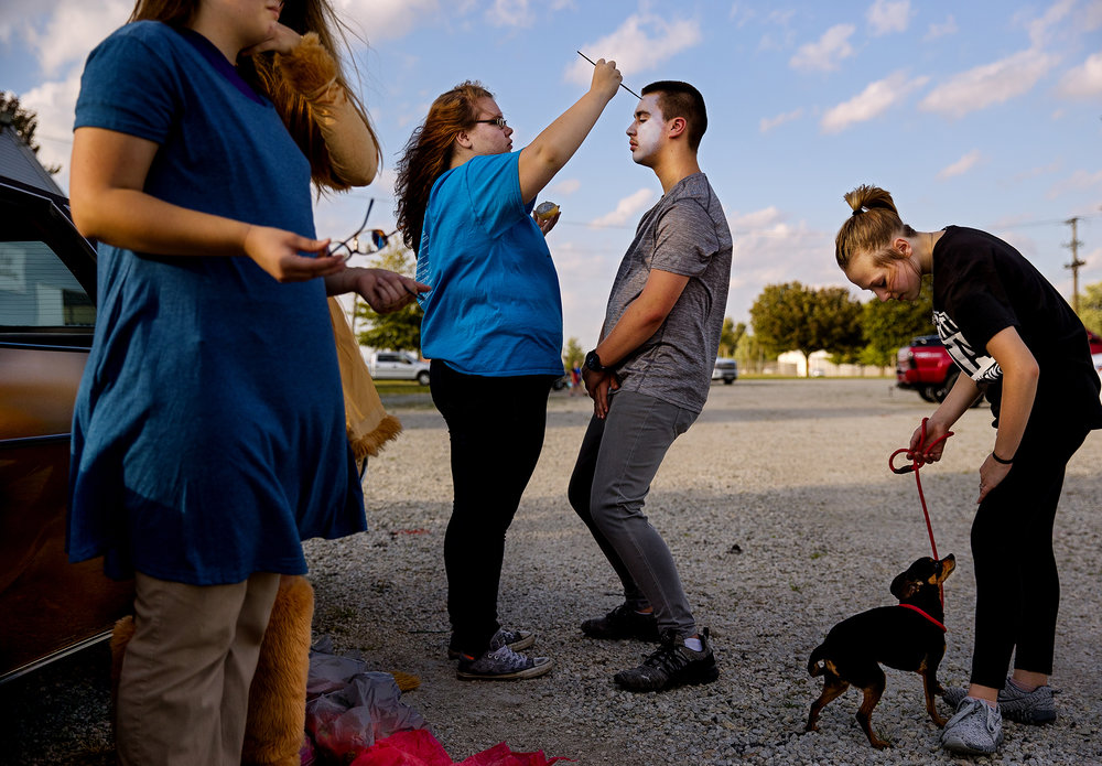 "Morgan Hogarth applies Tin Man make-up to Chase Hunsley's face as Kloey Locke tends to her dog, Lola, who was being conscripted into service as Toto, as they prepare to walk in the Taylorville High School homecoming parade as characters from the Wizard of Oz Wednesday, Oct. 3, 2018. The group, which also included a Dorothy and a Cowardly Lion, consisted of members of the school's library club that decided the musical logically matched this year's homecoming theme ""You'll always find your way home."" [Ted Schurter/The State Journal-Register]"