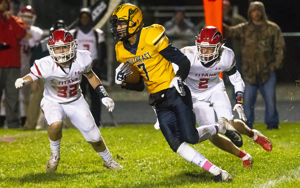 Southeast's Karlous Perry breaks loose of Glenwood's Jake Wooldridge, left, and Conley Price Friday, Oct. 12, 2018 at Southeast High School's Spartan Field in Springfield, Ill. [Rich Saal/The State Journal-Register]