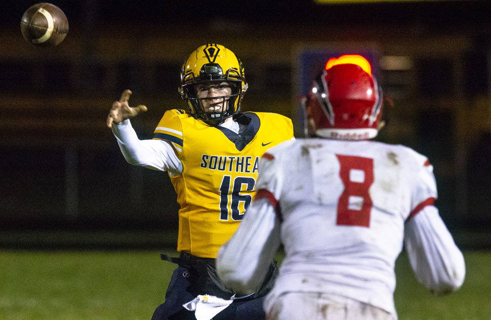 Southeast's Stuart Ross passes with Glenwood's Talen Vogler closing in Friday, Oct. 12, 2018 at Southeast High School's Spartan Field in Springfield, Ill. [Rich Saal/The State Journal-Register]