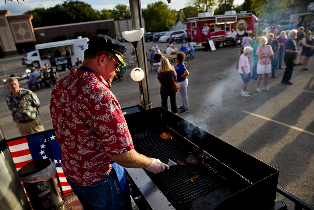 Jason Richardson, owner of Skipper's Island Oasis food truck, cooks a customer's order during the Appetite on the Avenue food truck event in the parking lot of Shop 'n Save on North Grand Avenue Tuesday, Oct. 9, 2018. [Ted Schurter/The State Journal-Register]