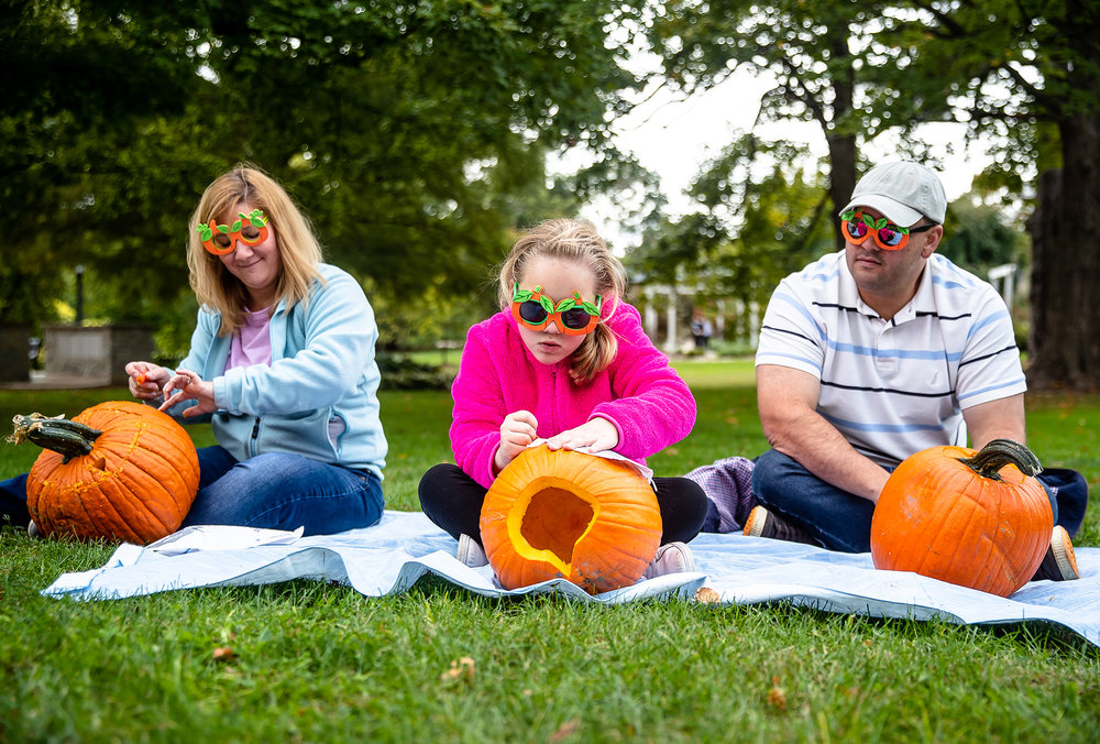Natalie Jacobs, 8, center, pokes small holes in to a pumpkin following a stencil while wearing pumpkin themed glasses she made with her father, Jon Jacobs, right, and mother Jennifer Jacobs, left, during the annual Carve For the Carillon at the Thomas Rees Memorial Carillon in Washington Park, Saturday, Oct. 13, 2018, in Springfield, Ill. The pumpkins carved during the Carve for the Carillon are put on display during next weekends'  Jack-O-Lantern Spectacular in Washington Park. The public can stop by and carve their own pumpkin as the event continues as long, as the pumpkin supply lasts, on Sunday from 11 a.m. to 4 p.m. [Justin L. Fowler/The State Journal-Register]