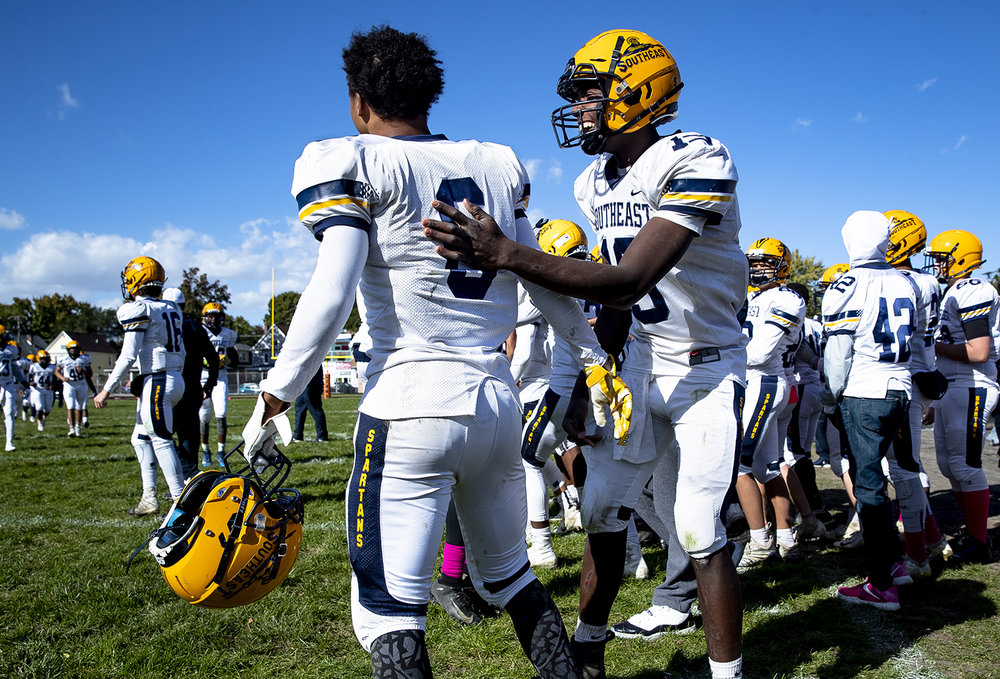 Southeast's Devin Blue-Robinson (19) and Deon Fairlee begin to celebrate their 44-12 win over Lanphier at Memorial Stadium Saturday, Oct. 20, 2018 in Springfield, Ill. [Rich Saal/The State Journal-Register]