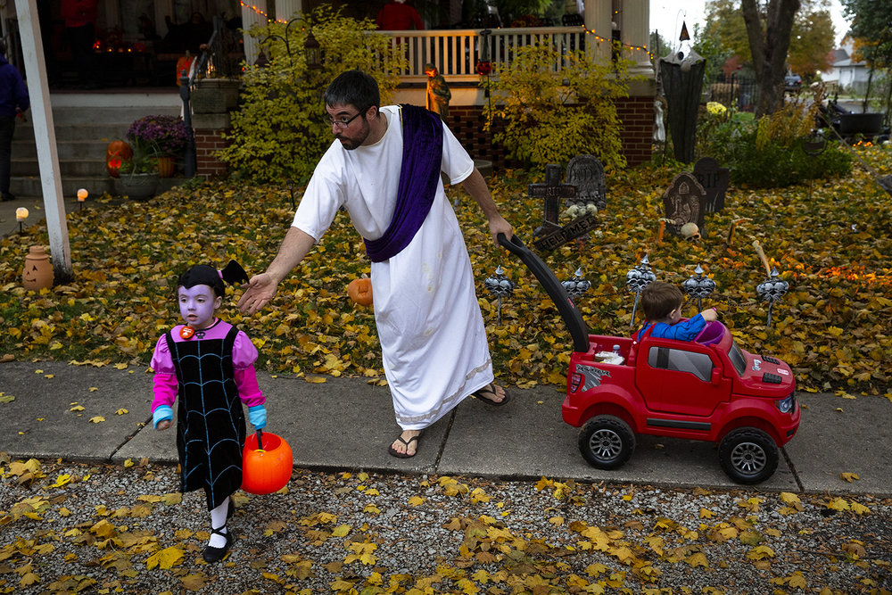 Chris Wiles directs his daughter Amelia, 4, to catch up with her sister, Lydia, while the family makes the rounds trick or treating Wednesday, Oct. 31, 2018 in Williamsville, Ill. In the wagon is Samuel Wiles, 2. [Rich Saal/The State Journal-Register]