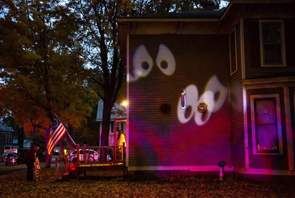 Ghosts projected on the side of a house keep an eye on things during Halloween trick or treating Wednesday, Oct. 31, 2018 in Williamsville, Ill. [Rich Saal/The State Journal-Register]