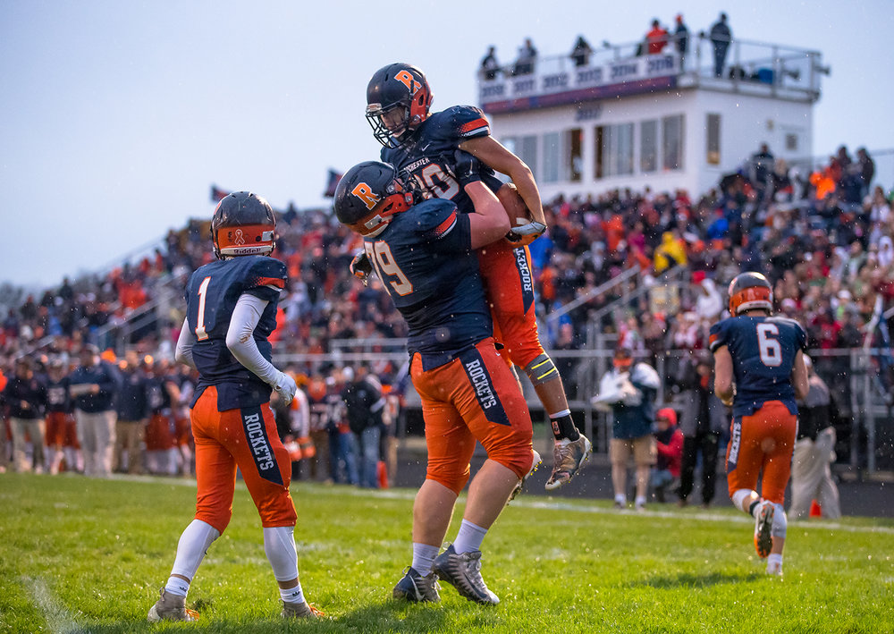 Rochester's Zach Gleeson (30) is hoisted up by Rochester's Tyler Wetherell (79) after scoring a touchdown against Pontiac in the first half in the second round of the Class 4A playoffs at Rochester High School, Saturday, Nov. 3, 2018, in Rochester, Ill. [Justin L. Fowler/The State Journal-Register]