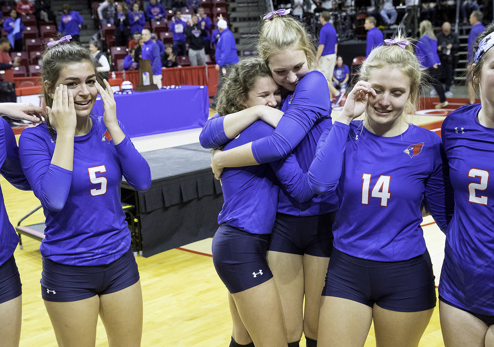 Flanked by Pleasant Plains' Emma Grieser, left, and Chloe Burt, Ali Fraase hugs Allie Edwards as the tearful Cardinals listen to head coach Denise Dufour tell the team she knew they would make it through a tough second game against Galena to win the the IHSA Class 2A Volleyball championship at Redbird Arena in Normal Saturday, Nov. 10, 2018. [Ted Schurter/The State Journal-Register]