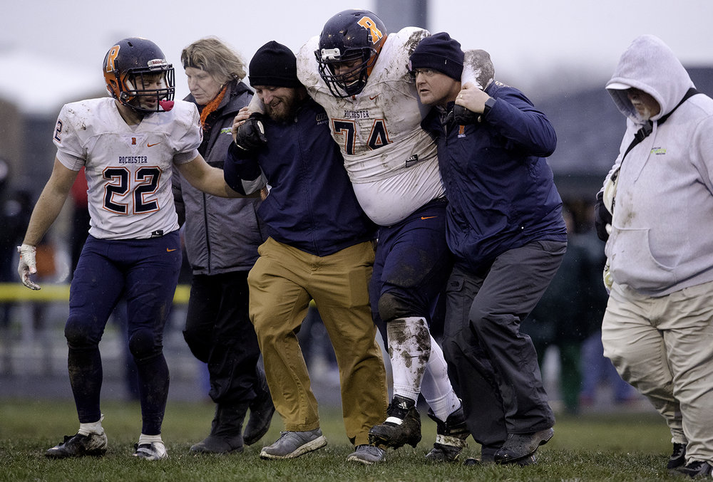 Rochester's Nathan Jackson is escorted off the field after an injury during the Class 4A semifinal at Kankakee Bishop McNamara Saturday, Nov. 17, 2018. [Ted Schurter/The State Journal-Register]
