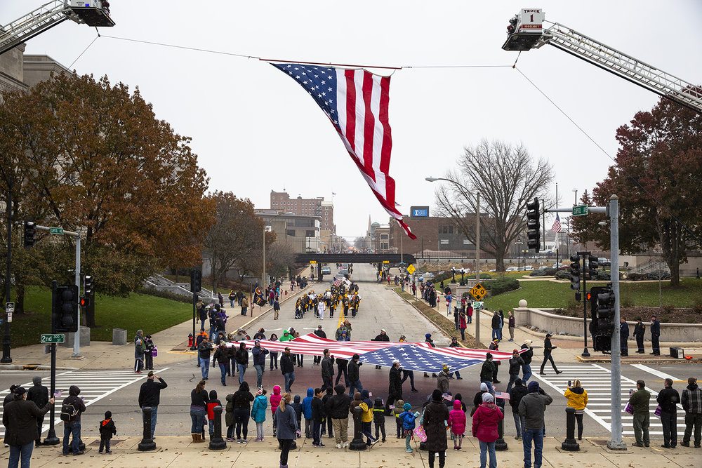 A large flag presented by the Springfield Elks Lodge 158 turns the corner at Second Street and Capitol Avenue, passing under another flag hoisted by the Village of Sherman and Springfield fire departments during the Veterans Day parade Monday, Nov. 12, 2018 in Springfield, Ill. [Rich Saal/The State Journal-Register]