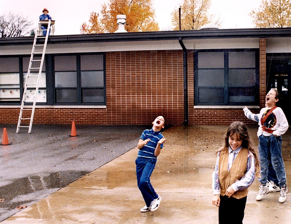 Students at Southern View Elementary School laugh at the the sight of their principal, Judy Walsh, having her lunch while sitting at a desk on the school roof Oct. 29, 1991. She promised the students that if they raised $200 for United Way, she would dine on the roof. [Bill Hagen/The State Journal-Register]