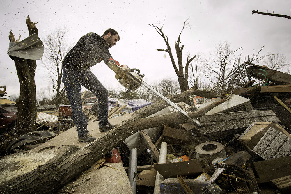 Steven Tirpak uses a chainsaw to remove tree branches that fell onto his two-story home in Taylorville Sunday, Dec. 2, 2018. Tirpak and his infant were not home when the storm struck. [Ted Schurter/The State Journal-Register]