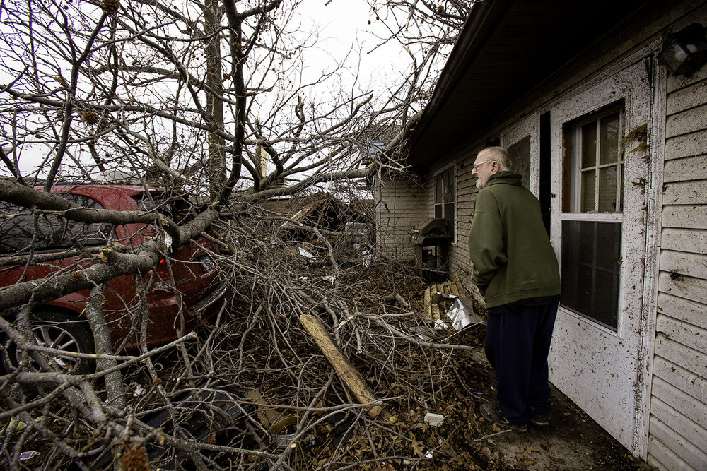 John Tilton glances at the tornado damage to the front yard of his Taylorville home Sunday, Dec. 2, 2018. Tilton and others at home took shelter in the bathroom during the tornado. [Ted Schurter/The State Journal-Register]