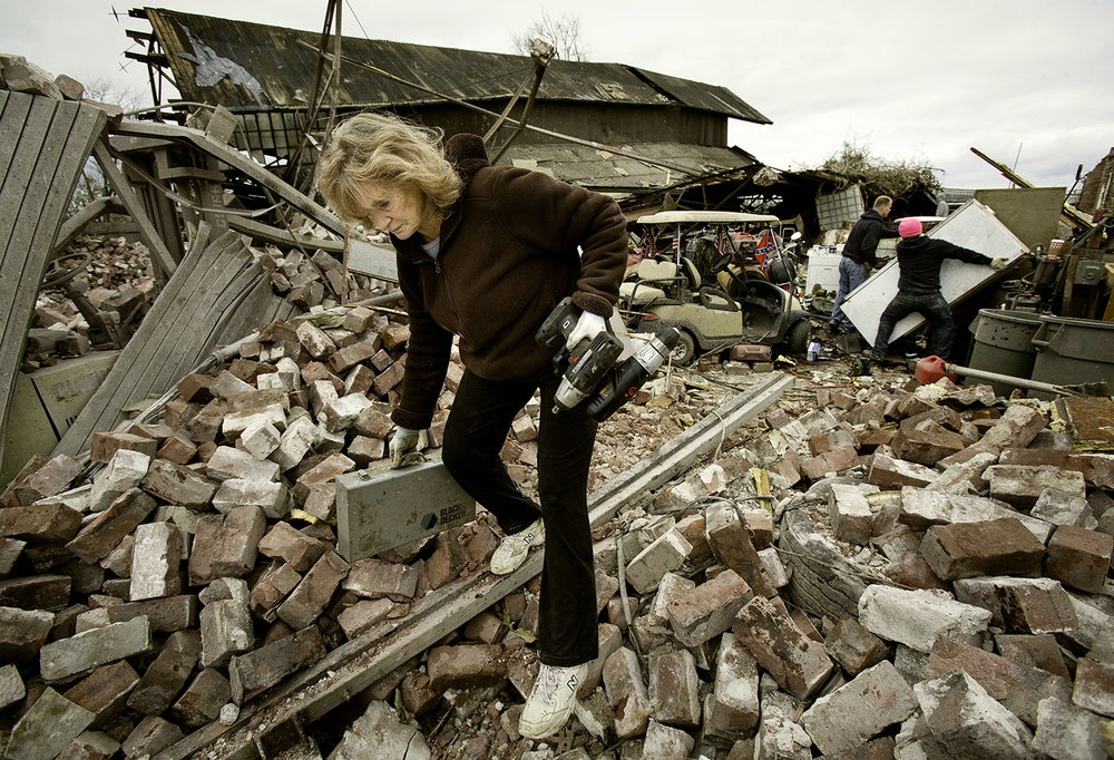 Marie Sheedy hauls salvageable items from the destroyed remains of her son Don's shop, an old train shed, as residents dig out and clean up tornado debris in Taylorville Sunday, Dec. 2, 2018. [Ted Schurter/The State Journal-Register]