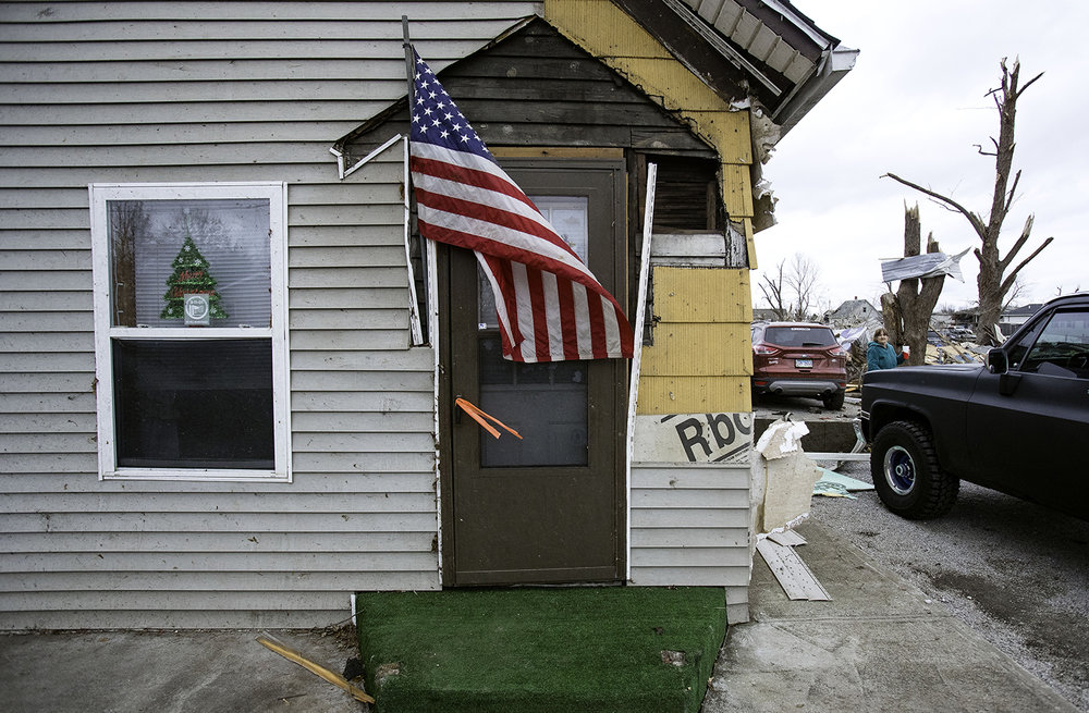 """Pete Barker of Harrisburg, Ill., wedged a makeshift flag pole in the front of his parent's tornado-damaged house in Taylorville Sunday, Dec. 2, 2018. Barker said his dad, a Vietnam veteran who is hospitalized for a heart attack he suffered during the storm, always had flags here. """"Dad wouldn't like us not having flags in front of the house right now."""" [Ted Schurter/The State Journal-Register]"""