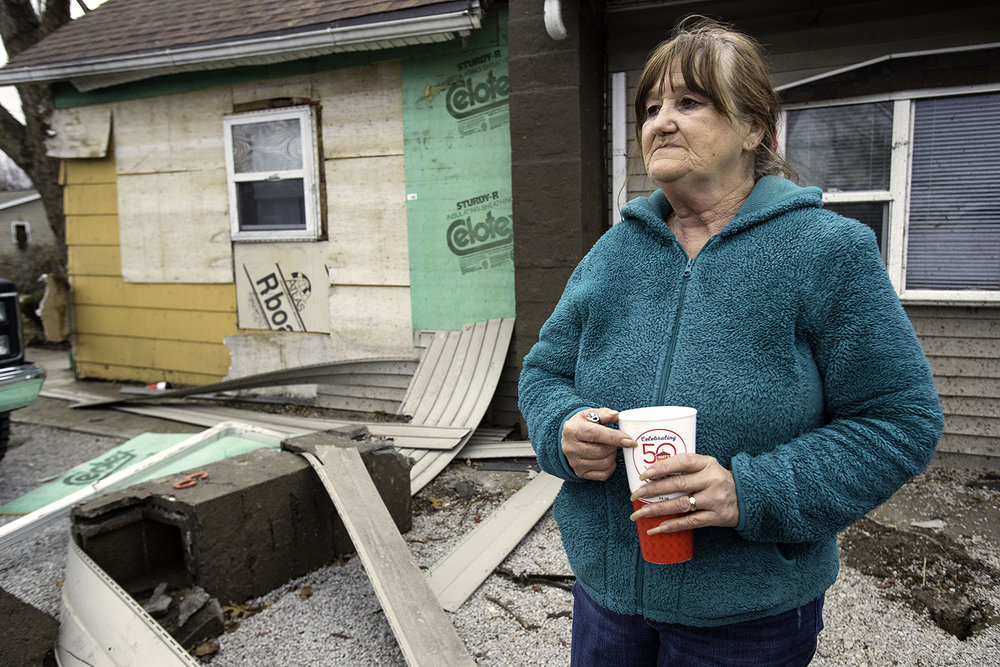 Vickie Barker watches as her neighors sort through the debris of their destroyed Taylorville home Sunday, Dec. 2, 2018. Barker said she watched from the window as it happened because she didn't want to leave her husband alone during the storm and he couldnt' get to the basement. Barker's roof was lifted off the home during the storm which among other things also destroyed her chimney and car port. [Ted Schurter/The State Journal-Register]