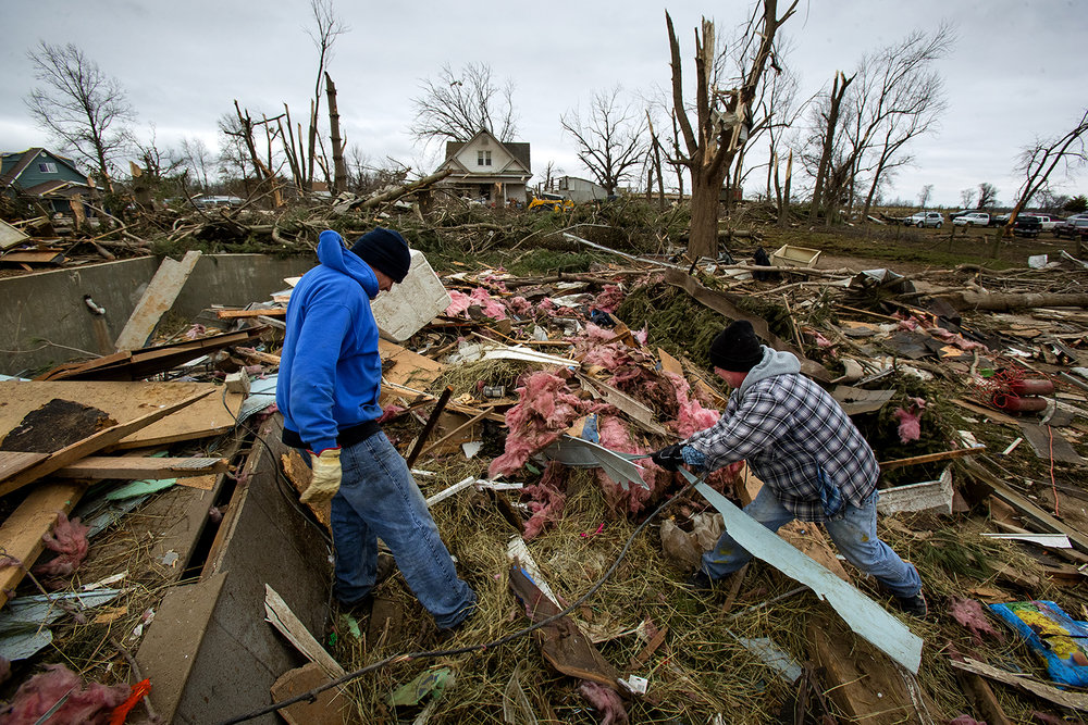 Jeremy Clayton, left, and Randy Campbell help clear debris from the site where Cherri McCullough's Taylorville home used to be Sunday, Dec. 2, 2018. The home was blown off it's foundation and destroyed. [Ted Schurter/The State Journal-Register]