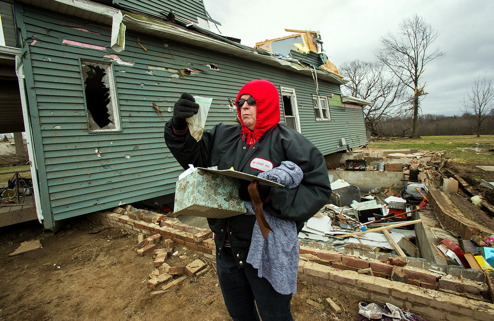 Georgi Adermann looks through some items she retrieved from her daughter Katie Hackney's home Sunday, Dec. 2, 2018. Hackney's home was blown off it's foundation during a tornado Saturday. [Ted Schurter/The State Journal-Register]