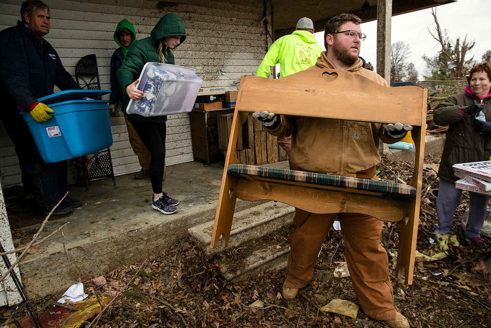 Friends, family and neighbors helped empty the tornado-damaged Taylorville home of Chris and Dennis Metsker Sunday, Dec. 2, 2018. A small army of helpers cleared downed trees, moved hay bales, cleaned-trash and moved items from the house onto trailers to take to storage. [Ted Schurter/The State Journal-Register]
