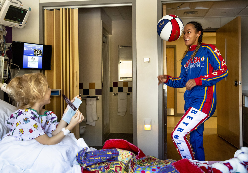 """Briana """"Hoops"""" Green, a member of the Harlem Globetrotters, visited HSHS St. John's Children's Hospital Tuesday, Nov. 27, 2018 in Springfield, Ill., where she shared a few of her tricks with Sara Mosher, 4 and other pediatric patients. Green joined the team three years ago, after playing college basketball for the University of Texas at El Paso. She´s part of the team´s Smile Patrol and is visiting cities to promote the team´s appearance at The Bank of Springfield Center on Dec. 9. [Rich Saal/The State Journal-Register]"""