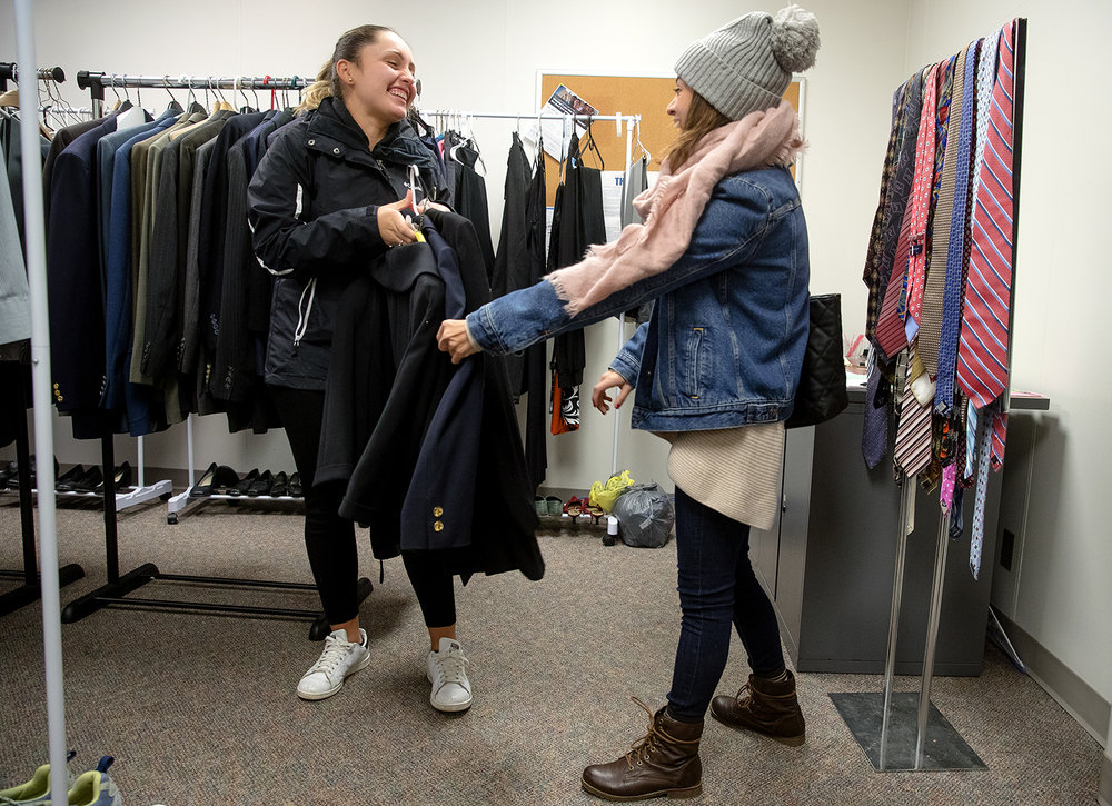 University of Illinois Springfield senior Maria Espinosa laughs with her roomate Sonia Hernandez as she shows her a few of the items she found at the UIS Professional Clothing Closet Thursday, Nov. 29, 2018. The closet is open to students annually in November in recognition of National Career Development Month and is operated by the Career Development Center. It features free professional and business casual attire to students including suits, blazers, skirts, button-down shirts, and more donated by UIS faculty, staff, friends of the college, and alumni. [Ted Schurter/The State Journal-Register]