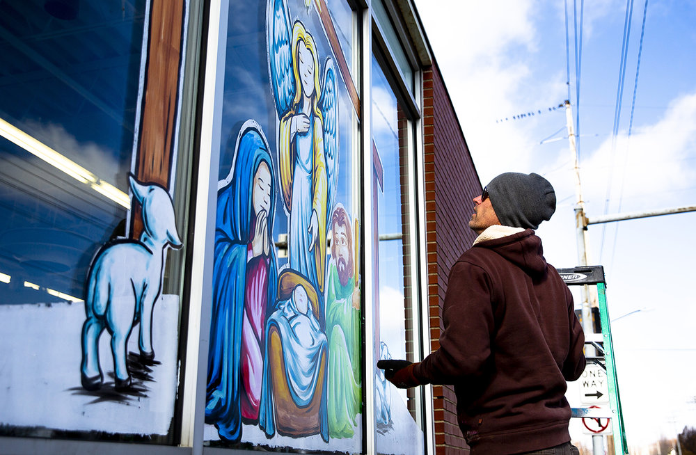 Artist Troy Freeman finishes up painting a nativity scene on the windows of the Salvation Army Family Store on 11th Street Wednesday, Dec. 5, 2018 in Springfield, Ill. Freeman was commissioned to create the artwork across the 75-foot window for the Christmas season. [Rich Saal/The State Journal-Register]