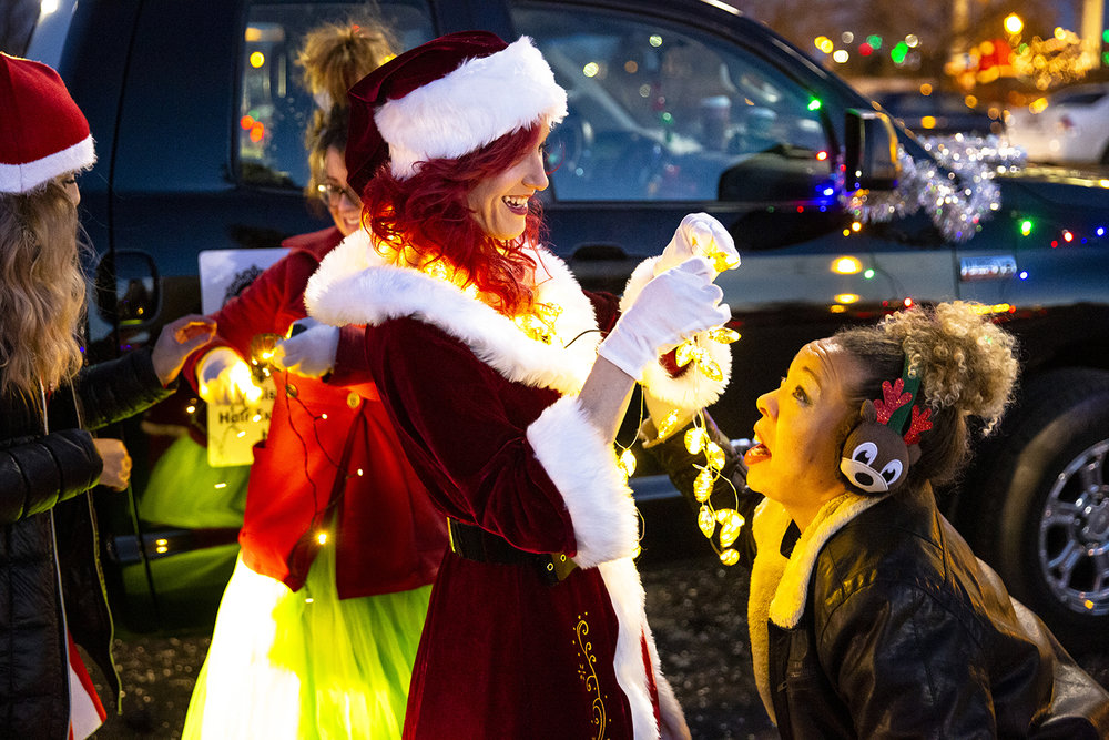 Brandy Kristin, center, owner of Unique Enhancements Salon and Gift Shoppe, helps put a set of holiday lights around Tami Klein's neck before the start of the Springfield Jaycees Holiday Lights Parade Saturday, Dec. 8, 2018 through downtown in Springfield, Ill. Kristin and the rest of her staff marched in the parade. [Rich Saal/The State Journal-Register]