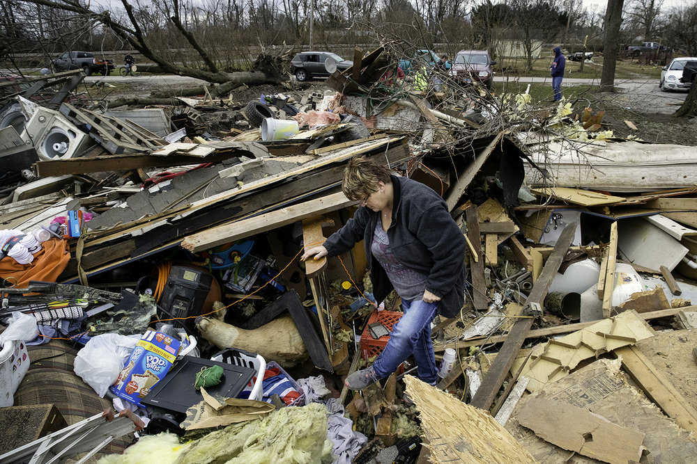 Joyce Morrissey sorts through the debris of her nephew Stephen Tirpak's house in Taylorville Sunday, Dec. 2, 2018. Morrisey said Tirpak and his infant daughter stayed with them last night and that she was looking for baby formula and clothes for her to wear. [Ted Schurter/The State Journal-Register]