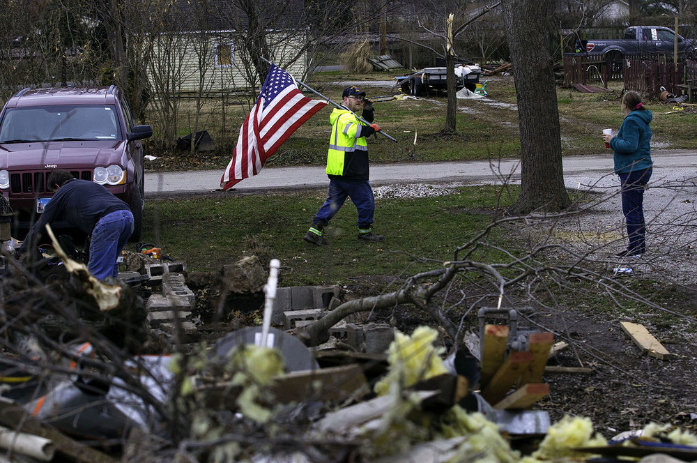 """Pete Barker of Harrisburg, Ill., carries a flag he got from a neighbor to put in front of his parent's tornado-damaged house in Taylorville Sunday, Dec. 2, 2018. Barker said his dad, a Vietnam veteran who is hospitalized for a heart attack he suffered during the storm, always had flags here. """"Dad wouldn't like us not having flags in front of the house right now."""" [Ted Schurter/The State Journal-Register]"""