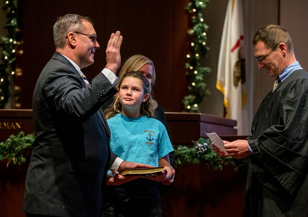 """Gianna Gray, 10, looks up at her father, Don Gray, as she holds the Bible for him to take the oath of office for Sangamon County Clerk from Circuit Judge John """"Mo"""" Madonia during a swearing-in ceremony in the Sangamon County Board Chambers at the Sangamon County Building, Monday, Dec. 3, 2018, in Springfield, Ill. [Justin L. Fowler/The State Journal-Register]"""