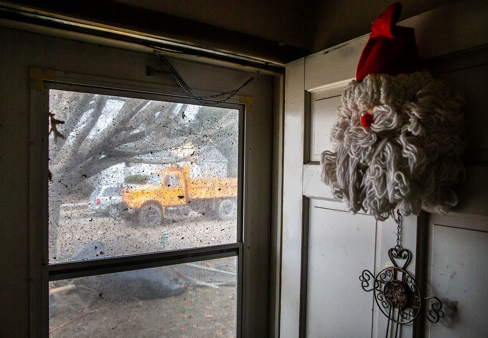 Debris is lodged in the screen with a Santa Claus hanging on the front door of Betty Layne's home as a dump truck waits to be filled up with debris as cleanup from Saturday's tornado continues along West Prairie Street, Monday, Dec. 3, 2018, in Taylorvile, Ill. [Justin L. Fowler/The State Journal-Register]