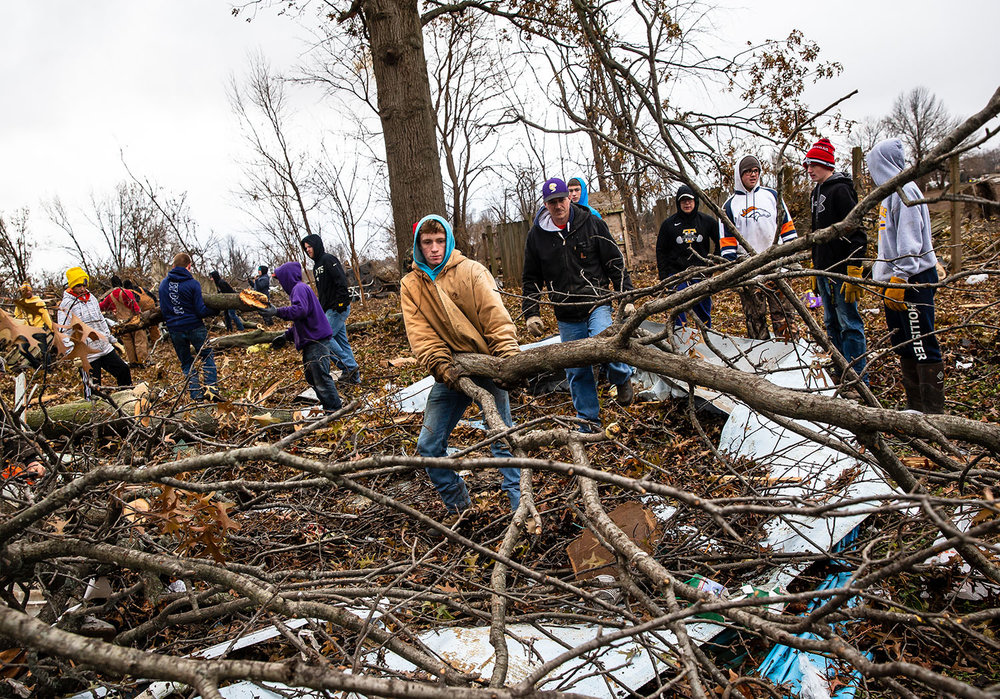 """Taylorville sophomore Wyatt Shirley, center, and Taylorville boys basketball head coach Ryan Brown remove fallen branches from behind a tornado damaged home as they join in with student athletes from Taylorville High School as they volunteer as a group to help with the cleanup from Saturday's tornado along West Prairie Street, Monday, Dec. 3, 2018, in Taylorvile, Ill. """"They don't have to come out here, but it's just a bunch of go getters that just wanna work and help,"""" said Brown of the athletes volunteering their time. """"It's not much different than being on the field or the wrestling mat or the basketball court, it's just people that wanna help."""" The athletes and their coaches went from house to house or wherever they were needed to help move debris to the curb. """"We've been through so many houses, I don't even know what road I'm on right now,"""" said Brown. """"I don't know who lives at this house or the last house or the house before that and that's how these kids are, here's a pile lets go move it."""" [Justin L. Fowler/The State Journal-Register]"""