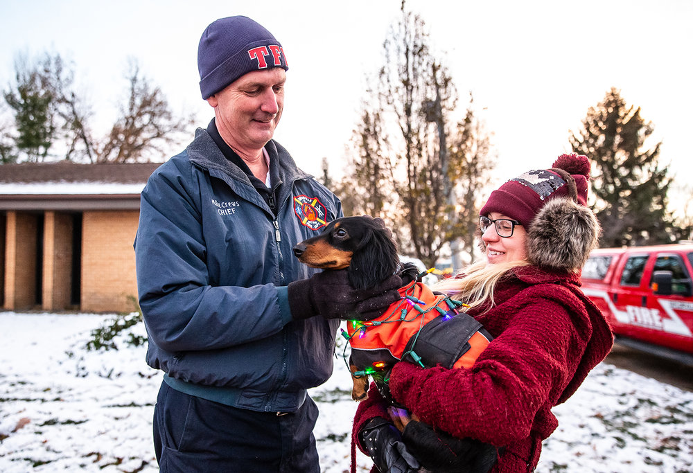 Taylorville Fire Chief Mike Crews visits with Brittany Moore and her dog, Boyd, dressed in Christmas lights, as he gets ready to march in the Taylorville Christmas Parade, Saturday, Dec. 8, 2018, in Taylorville, Ill. The parade was set to step off last Saturday and was cancelled right before a tornado hit the town. [Justin L. Fowler/The State Journal-Register]