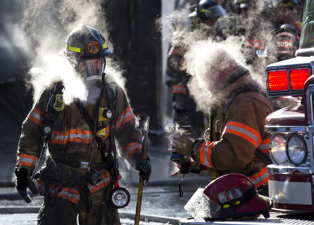 "Steam rises off two Springfield firefighters who caught a break after battling a house fire in the 3100 block of Victoria Drive Monday, Jan. 1, 2018. According to Chris Richmond, fire marshal for the Springfield Fire Department, neighbors reported a small explosion about 1:15 p.m., and heavy flames were showing from the garage area when firefighters arrived at the address. An adult male who appeared to have been working in the garage was injured and was transported to the hospital in stable condition, Richmond said. The temperature was just 2 degrees made for a ""very challenging environment,"" Richmond added. ""It typically slows us down a just little bit and makes our work cycles shorter. We have work cycles that are closer to 15-20 minutes before we cycle guys out"" for recovery. [Rich Saal/The State Journal-Register]"