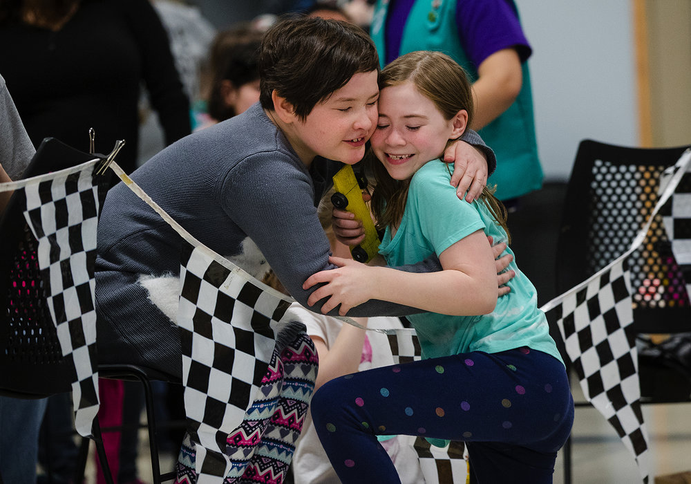 Keyra Schmidt, left, hugs her friend Sylvia Reynolds after she won her race during the Girl Scout Powderpuff Derby at Sherman United Methodist Church Saturday, Jan. 27, 2018. [Ted Schurter/The State Journal-Register]