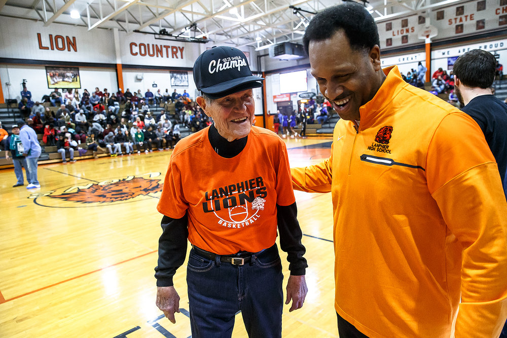 Former Lanphier athletic director and coach Arlyn Lober walks off the court with Principal Artie Doss after the 1983 State Championship team was honored during halftime as the Lions take on Decatur MacArthur at Lober-Nika gymnasium, Saturday, Feb. 10, 2018, in Springfield, Ill. [Justin L. Fowler/The State Journal-Register]
