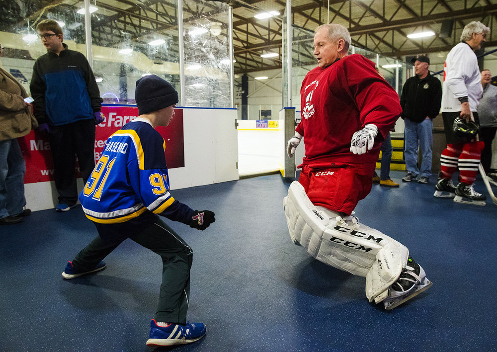 "Raymond Schneider mimics Bishop Thomas John Paprocki after asking him how easy it is to get into the goalie position before the 8th annual ""Hockey with Bishop Paprocki"" at the Nelson Center Thursday, February 28, 2018. The fundraiser benefits Catholic Charities Legal Services, an organization that  offers pro bono legal services to people with little to no income. [Ted Schurter/The State Journal-Register]"