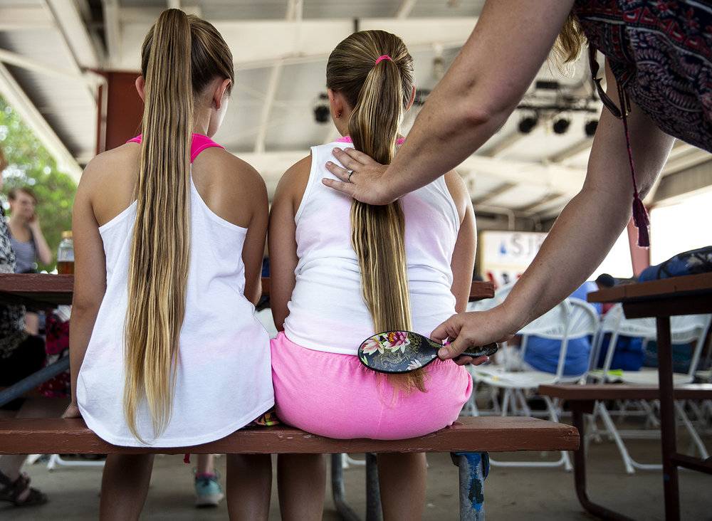 Alyssa Lynn Brickey, left, and her cousin, Braley Lynn Brickey, both from Jacksonville, have their ponytails combed by Alyssa's mother, Jane Kamp, before the ponytail contest on the Lincoln Stage at the Illinois State Fair Saturday, Aug. 11, 2018 on the fairgrounds in Springfield, Ill. [Rich Saal/The State Journal-Register]