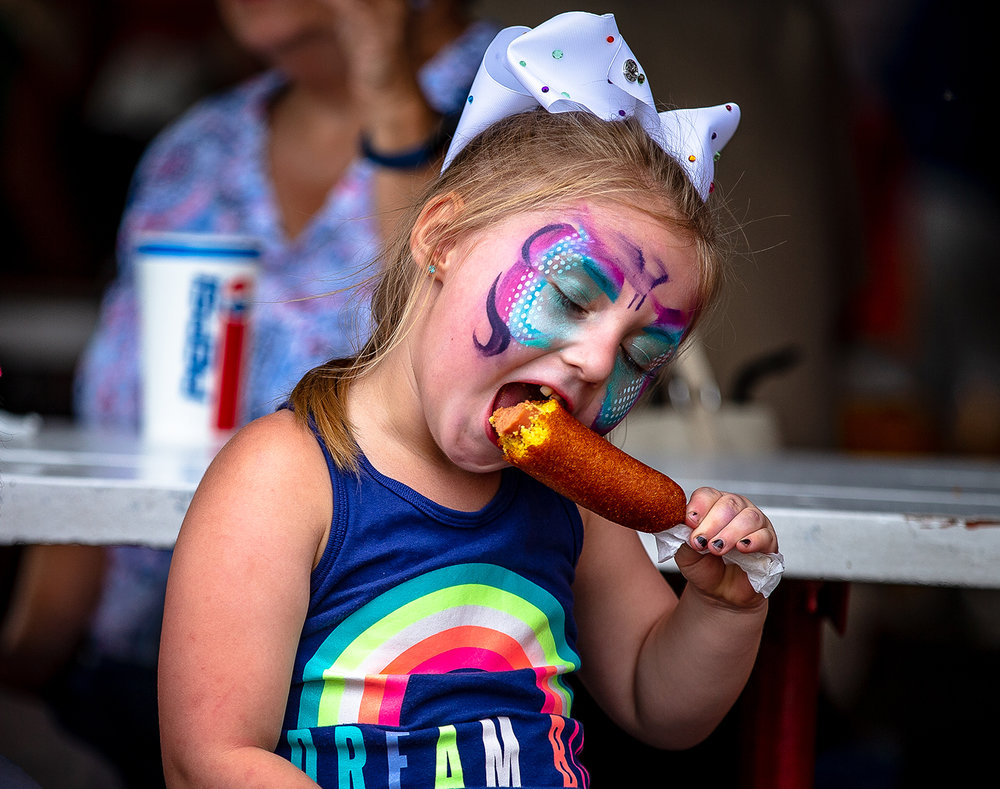 Olivia Townsend, 4, of Mechanicsburg, Ill., tries out her first corndog from Vose's Korndogs on the final day of the Illinois State Fair at the Illinois State Fairgrounds, Sunday, Aug. 19, 2018, in Springfield, Ill. [Justin L. Fowler/The State Journal-Register]