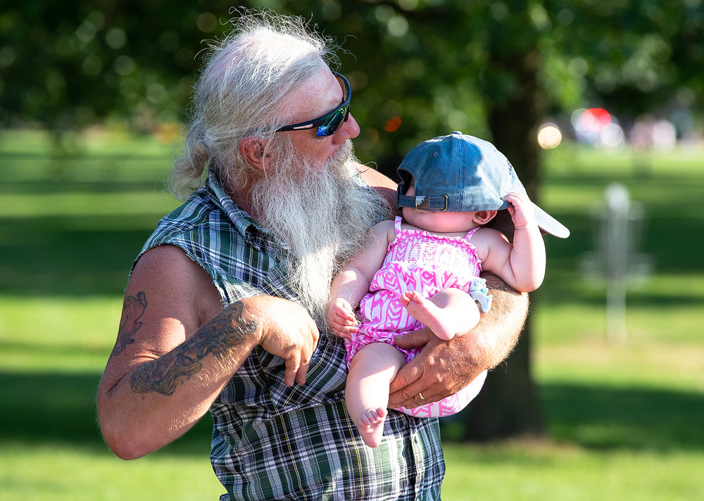 David Mahler holds his granddaughter Avie Mahler as the Illinois State Fair Twilight Parade passes by in Lincoln Park, Thursday, Aug. 9, 2018, in Springfield, Ill. [Justin L. Fowler/The State Journal-Register]
