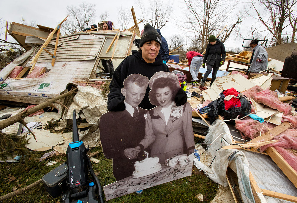 "Tiffani Bailey carries an enlarged wedding photo of her grandparents, Charles and Betty Bailey, from the debris of her destroyed home in Taylorville. Bailey, who was in the trailer with her son and mom when it was hit, damaged her ribs and needed more than 30 stitches. ""It's a miracle I'm alive. I was in this trailer when it got hit. I lost everything, though. I got nothing,"" she said. [Ted Schurter/The State Journal-Register]"