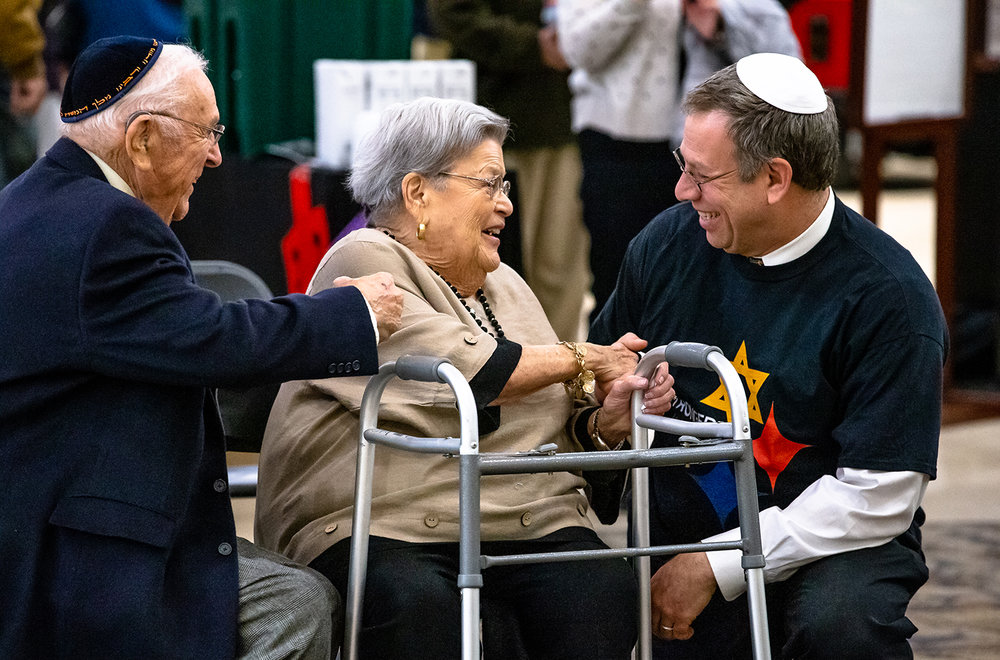 Dr. Marc Garfinkel, right, visits with Betty Hurwitz, center, and her husband Ralph, left, after they all were honored with lighting the Menorah during the public Menorah lighting at White Oaks Mall, Thursday, Dec. 6, 2018, in Springfield, Ill. Garfinkel is a native of Pittsburgh, Penn., and was a member of the Tree of Life Synagogue where a gunman killed 11 people in October. [Justin L. Fowler/The State Journal-Register]