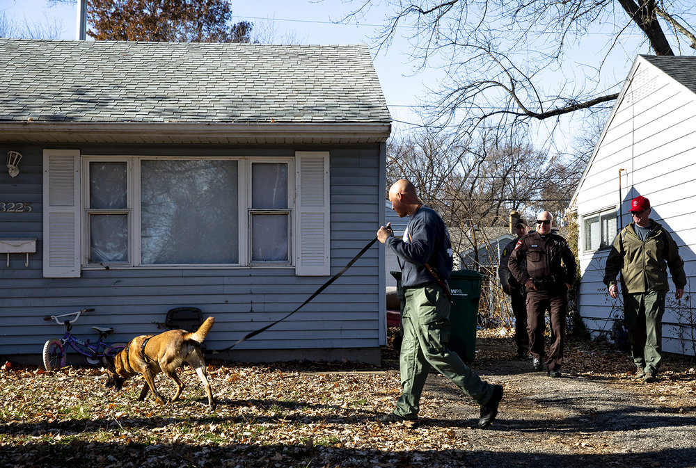 Sangamon County sheriff's deputy Drew Dickason and his K-9 partner, Rajah, search the 3200 block of Normandy for a trail that could have been left by a suspect in an armed robbery that occurred near Security Bank and the Bank of Springfield at Stevenson Drive and Lake Plaza Drive Tuesday, Dec. 11, 2018 in Springfield, Ill. [Rich Saal/The State Journal-Register]