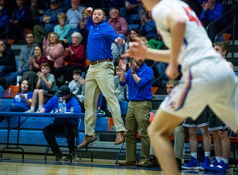 Auburn head coach Seth McCoy leaps into the air as he encourages the Trojans to get back down the court against Riverton at Riverton High School Tuesday, Dec. 18, 2018. [Ted Schurter/The State Journal-Register]