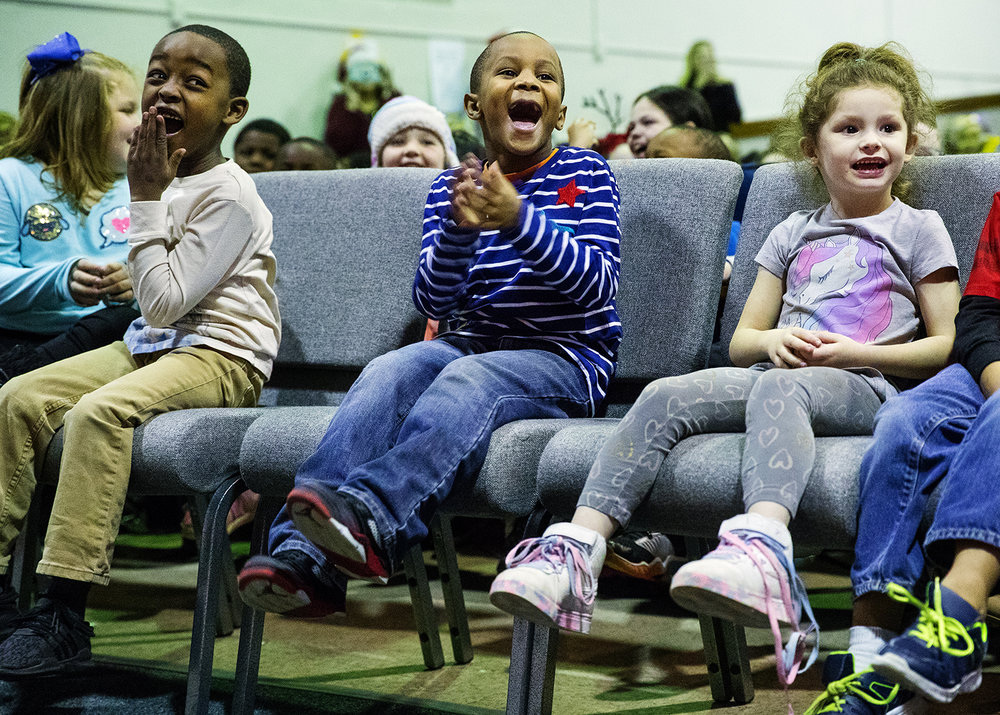 Kindergarteners Davon Montgomery, left, Marcus Henry and La-Anjel Freligh cheer as Santa Claus makes an appearance on stage during a special ceremony at Feitshans Elementary School Tuesday, Dec. 18, 2018. Santa and a few helpers distributed a stocking to 375 students that included brand new school-spirit wear and a candy cane. The stockings and gifts were donated by the employees of Horace Mann who also gave each school employee a Hyvee gift card. 