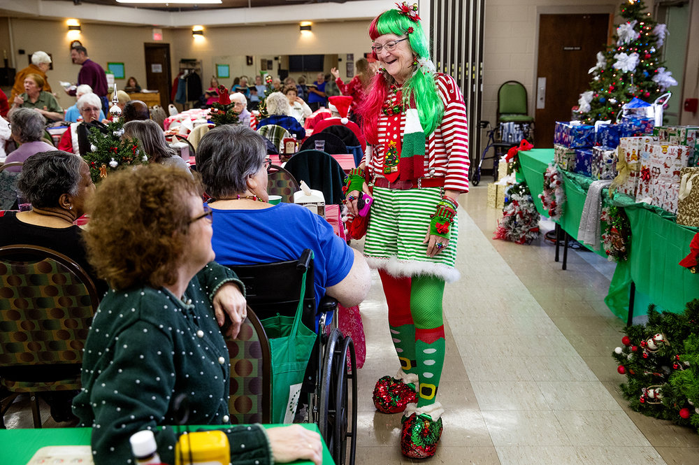 Darlene Freeman, left, chats with Judi Weaver about her homemade elf outfit that she wore for the Christmas Party at Senior Services of Central Illinois Wednesday, Dec. 19, 2018. Weaver adorned her outfit with jingle bells, ornaments, faux fur and colored hair. The party featured Santa Bingo, live music and Christmas carols. [Ted Schurter/The State Journal-Register]
