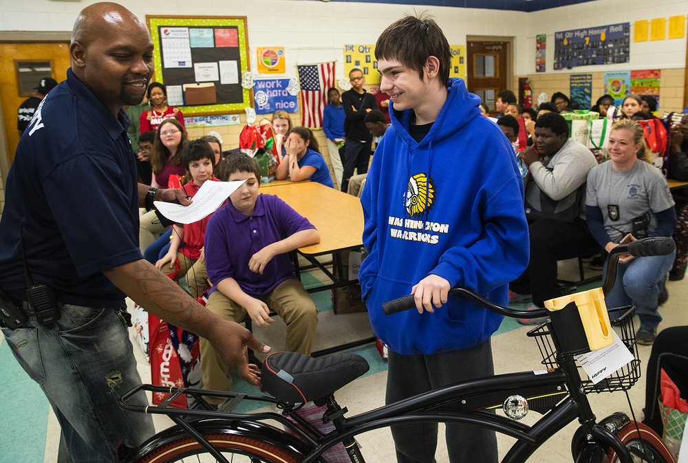 "Darryl Williams presents Grant Saccaro with a new bike during the ""Fifty Smiles"" event at Washington Middle School Thursday, Dec. 20, 2018. Williams uses donations from school teachers, administrators, local fraternities and sororities, and the union representing Springfield Police officers to purchase gifts personalized for the recipient. Saccaro and his family were recently displaced by a house fire and he said he'd ride the bike from the hotel where they're staying to school. [Ted Schurter/The State Journal-Register]"