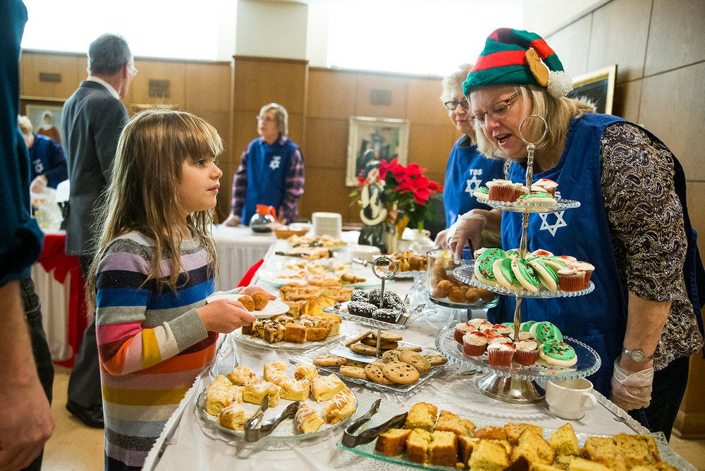 Sky Hirshfield, 6, left, gets assistance picking a treat from the dessert table from volunteer Jean Ferratier, right, during the 15th annual Holiday Interfaith Breakfast at the Tmeplbe B'rith Sholom, Tuesday, Dec. 25, 2018, in Springfield, Ill. Proceeds from the breakfast benefit Compass For Kids, a local program with school-year and summer programs to support at-risk children in Springfield School District 186. [Justin L. Fowler/The State Journal-Register]