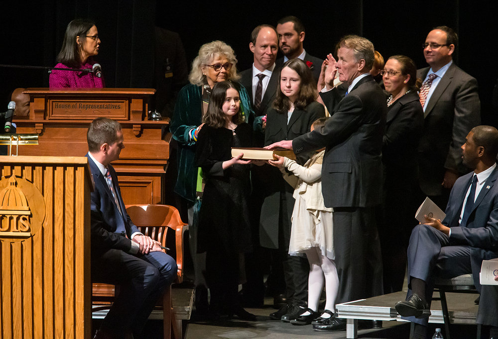 Illinois Speaker of the House Michael Madigan, D-Chicago, is sworn in as the Illinois Speaker of the House by his daughter, Attorney General Lisa Madiagan, left, for his 19th term while being surrounded by his family during the inauguration ceremony for the Illinois House of Representatives for the 101st General Assembly at the University of Illinois Springfield's Sangamon Auditorium, Wednesday, Jan. 9, 2019, in Springfield, Ill. [Justin L. Fowler/The State Journal-Register]